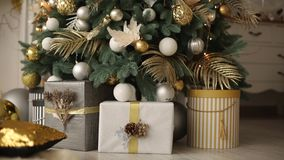 Stylish white interior with handmade gifts and presents decorated with ribbons and bumps under the Christmas tree. Comfort home full of golden decorations stock video