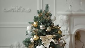 Stylish white New Year Eve interior design with decorated fir trees. Comfort home with Christmas tree full of golden. Decorations, lights and garlands stock video footage