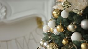 Stylish white New Year Eve interior design with decorated fir trees. Comfort home with Christmas tree full of golden. Decorations, lights and garlands stock footage