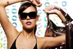 Stylish woman. Young beautiful woman with fashion sunglasses holding handbag Stock Image
