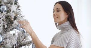 Stylish woman admiring a Christmas tree Stock Photo