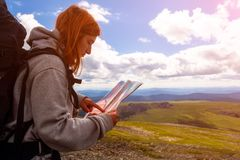 Stylish woman with backpack hiking. Orient themselves to the terrain, study map and navigate the route through the mountains. Travel Lifestyle and survival stock images