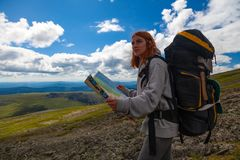 Stylish woman with backpack hiking. Orient themselves to the terrain, study map and navigate the route through the mountains. Travel Lifestyle and survival royalty free stock photo