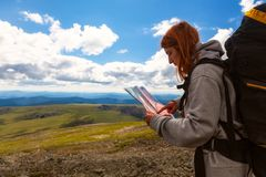 Stylish woman with backpack hiking. Orient themselves to the terrain, study map and navigate the route through the mountains. Travel Lifestyle and survival stock image