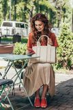 Stylish woman with bag using smartphone while sitting on terrace. In cafe royalty free stock photography