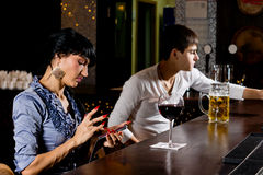 Stylish woman at the bar sending an sms message. Stylish young women sitting at the counter at the bar sending an sms message on her mobile phone, side view royalty free stock images