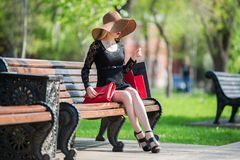 Stylish woman in black dress and hat with shopping bags sitting on a bench in the park. Holiday concert Stock Photography