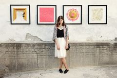 Stylish woman with boho outfit posing at wall with street art in royalty free stock images