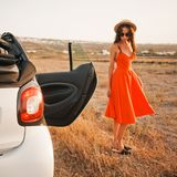 Stylish woman at car cabriolet. Outdoor lifestyle photo of beautiful stylish woman at car cabriolet. Holiday and travel. Summer trip. Freedom, youth and carefree Stock Photos