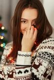 Stylish woman in christmas lights posing and smiling at christma Stock Photo