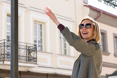Stylish Woman in a City Waving her Hand and Smiling Royalty Free Stock Photo
