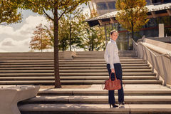Stylish woman climbing a flight of urban stairs. Stylish woman in slacks carrying a handbag climbing a flight of concrete outdoor urban stairs pausing to turn Stock Image