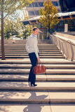 Stylish woman climbing a flight of urban stairs. Stylish woman in slacks carrying a handbag climbing a flight of concrete outdoor urban stairs pausing to turn Stock Photos