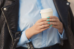 Stylish woman with colorful manicure in leather jacket holding in hands a paper cup of coffee. Outdoors Royalty Free Stock Images