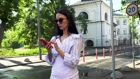 Stylish woman dial number on phone and start talking standing at urban street. Elegant woman in sunglasses, white skirt and stripped blouse is standing at urban stock footage