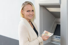 Stylish woman drawing money at a bank ATM Royalty Free Stock Images