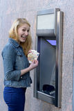 Stylish woman drawing money at an outdoor bank ATM Stock Images