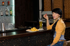 Stylish woman drinking alone at the bar counter royalty free stock photos