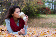 Stylish woman drinking coffee while lying down on autumn leaves Stock Photos