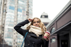 Stylish woman drinking coffee to go in a city street. Young blonde drinking coffee outside on a cloudy day Stock Images