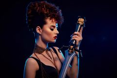 Stylish woman with fashionable hairdress holding steel sword. stock photos