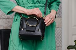 Stylish woman with a fashionable woman has a small black bag cl royalty free stock images