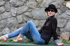 Stylish woman with glasses and hat. A portrait of a stylish woman with glasses and hat sitting on a bench Royalty Free Stock Photos