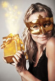 Stylish woman with golden mask and gift. Stylish woman wearing golden mask and holding gift box, celebrating holidays, female receive gold Christmas present, new Stock Photo
