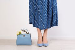 Stylish woman with handbag and spring flowers. Near light wall royalty free stock image