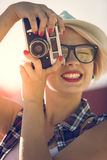 Stylish woman in hat making photo with film camera at sunset Royalty Free Stock Images