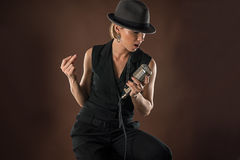 Stylish woman in a hat with a retro microphone Royalty Free Stock Photography