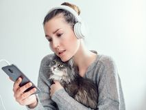 Stylish woman in headphones and with her kitten. Stylish, young woman in headphones and with mobile phone, gently hugging her kitten on a white background Stock Images