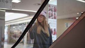 Stylish woman hipster going up escalator in a mall.  stock video footage