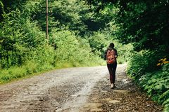 Stylish woman hipster traveler walking on the road with backpack Royalty Free Stock Image