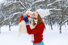 Stylish woman holding a dog and kisses him Royalty Free Stock Photo