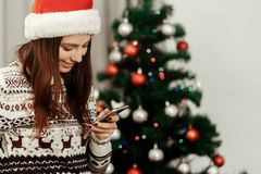 Stylish woman holding phone looking at screen at christmas tree Stock Image