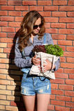 Stylish woman is holding in their hands a linen bag full of fresh lettuce salad Stock Photo