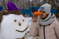 Stylish woman holds a big carrot, the nose of a real big snowman. Beautiful woman has fun in winter park, wintertime. Stylish woman holds a big carrot, the nose Stock Photo