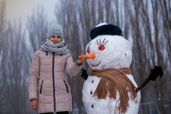 Stylish woman holds a big carrot, the nose of a real big snowman. Beautiful woman has fun in winter park, wintertime Stock Images