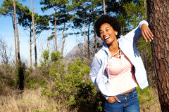 Stylish woman leaning on tree trunk and smiling Royalty Free Stock Photo