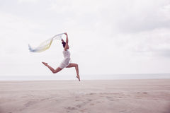 Stylish woman leaping with scarf Stock Image