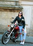 Stylish woman in leather jacket on classic motorcycle in town Royalty Free Stock Images