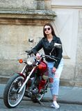 Stylish woman in leather jacket on classic motorcycle in town Stock Photography