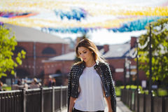 Stylish woman in a leather jacket walks around the city. Look back Royalty Free Stock Photography