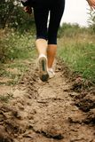 Stylish woman legs in sneakers walking on ground, exercise outdo. Ors Royalty Free Stock Photo