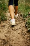 Stylish woman legs in sneakers walking on ground, exercise outdo. Ors Royalty Free Stock Photography