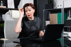 Stylish woman lifted her glasses and looks right sitting at table in office. Adult woman at computer. portrait of Strict businesswoman holding hand glasses for royalty free stock image