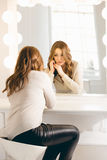 Stylish woman looking in her reflection at mirror with bulbs Royalty Free Stock Image