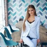 Stylish woman in modern interior. Young beautiful woman with long straight blond hair in blue suit sitting at wooden table in stylish modern interior. Natural Royalty Free Stock Photo