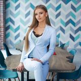 Stylish woman in modern interior. Young beautiful woman with long straight blond hair in blue suit sitting at wooden table in stylish modern interior. Natural Royalty Free Stock Photos